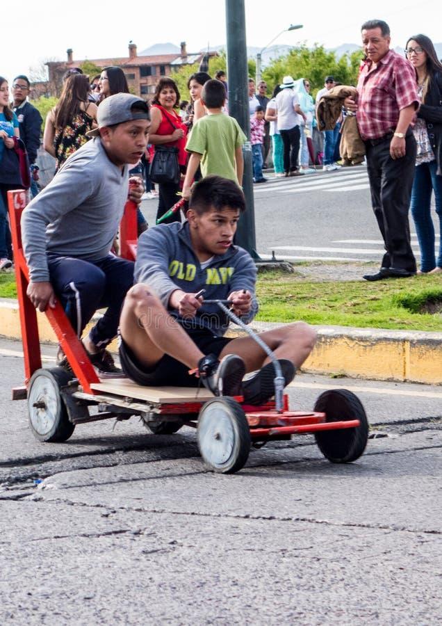 Dzieciaki ścigają się wokoło kąta na domowej roboty drewnianych samochodach wyścigowych zdjęcia royalty free