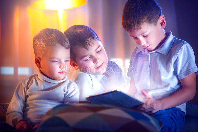 Dzieciaki bawić się gry na pastylka komputerze osobistym Trzy chłopiec z pastylka komputerem zdjęcie stock