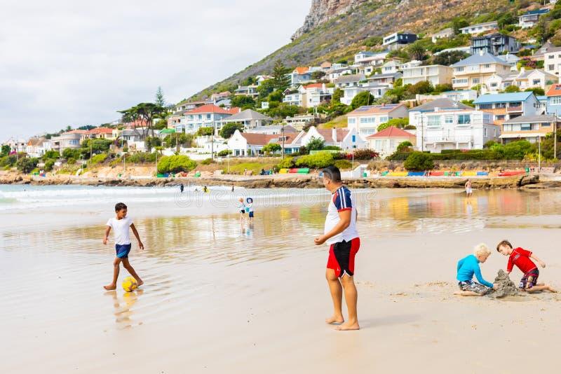 Dzieciaki bawić się na Rybim Hoek wyrzucać na brzeg na chmurnym dniu zdjęcie stock