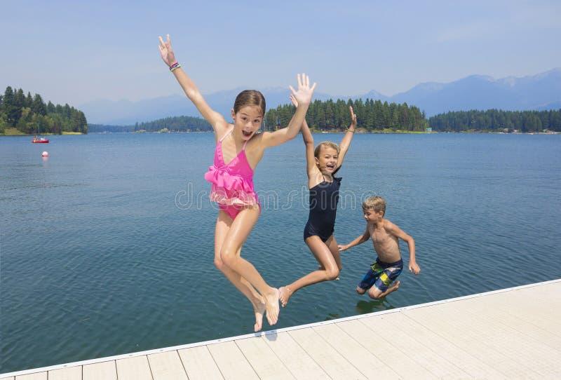 Dzieciaki bawić się przy jeziorem na ich wakacje zdjęcie royalty free