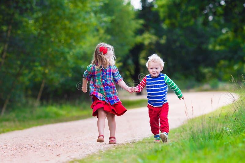 Dzieciaki bawić się w jesień parku zdjęcie royalty free