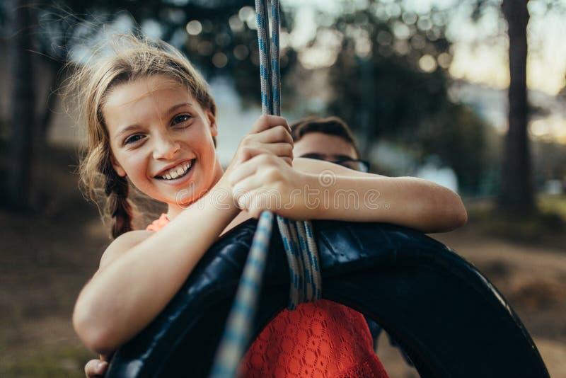 Dzieciaki bawić się w parku na opony huśtawce zdjęcia royalty free