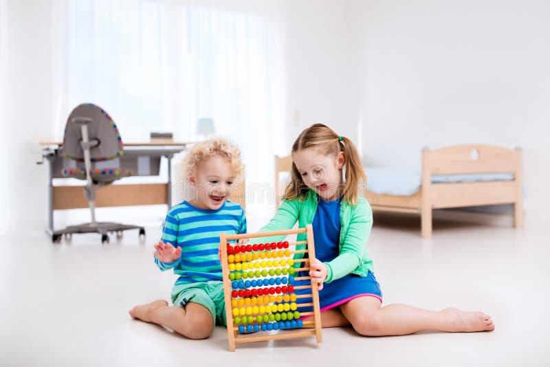 Dzieciaki bawić się z drewnianym abakusem edukacyjna zabawka obraz stock