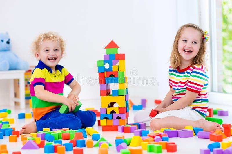 Dzieciaki bawić się z kolorowymi zabawkarskimi blokami fotografia stock