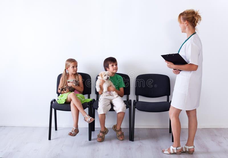 Dzieciaki bierze ich zwierzęta domowe weterynaryjna lekarka obrazy royalty free