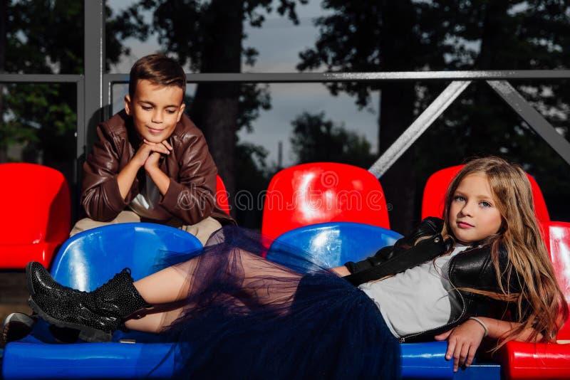 Dzieciaki chłopiec i dziewczyny obsiadanie w trybuna klingerytu szkolnych krzesłach zdjęcie stock