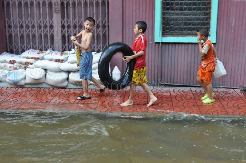 Dzieciaki cieszą się powódź z ich ciężarową oponą w zalewającej ulicie Bangkok, Tajlandia, na 30 2011 Listopadzie obrazy royalty free