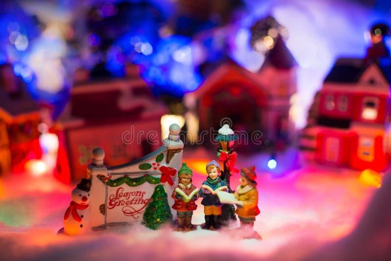 Dzieciaki czyta biblię obok wakacyjnego powitanie znaka z śnieżną boże narodzenie wioską w tle Wakacyjny powitanie miniatury scen zdjęcia stock