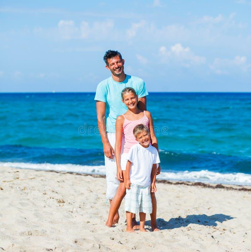 Dzieciaki i ojciec bawić się na plaży obrazy royalty free