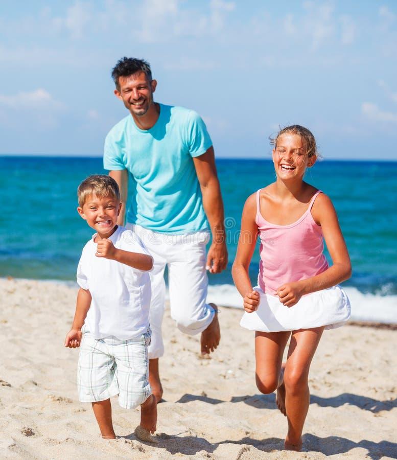Dzieciaki i ojciec bawić się na plaży obraz stock