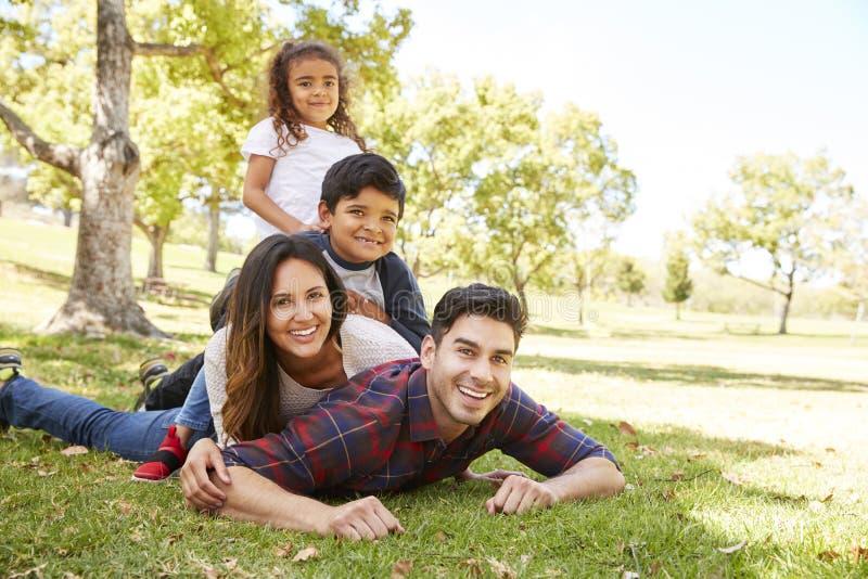 Dzieciaki i rodzice kłama w stosie na trawie w parku obraz stock