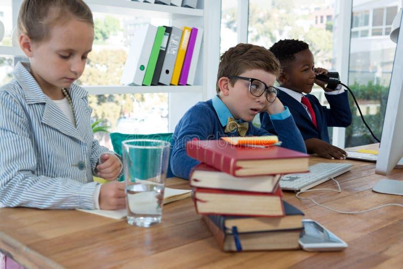 Dzieciaki jako dyrektory wykonawczy pracuje wpólnie obrazy stock