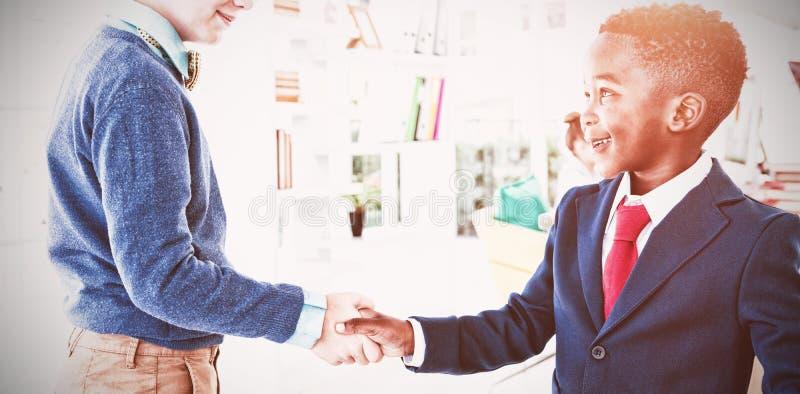 Dzieciaki jako dyrektory wykonawczy trząść ręki zdjęcie royalty free