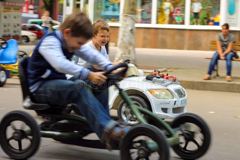 Dzieciaki jedzie zabawkarskiego samochód w sztuka terenie Nikolaev, Ukraina obrazy royalty free