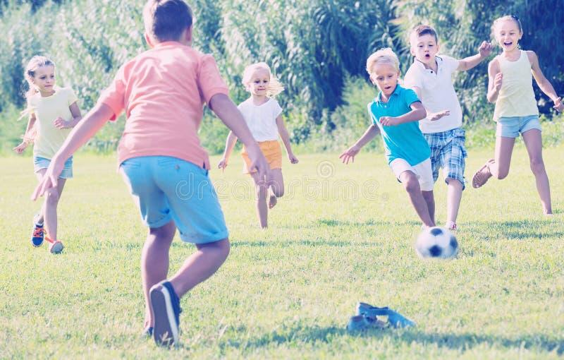 Dzieciaki kopie futbol w parku fotografia stock