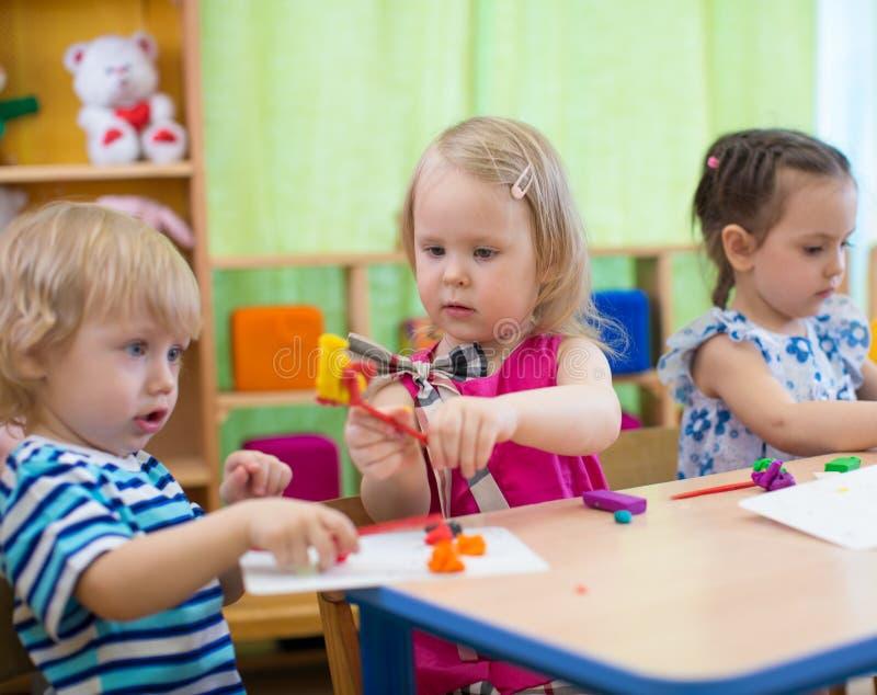 Dzieciaki lub dzieci tworzy sztuki i rzemiosła w dziecinu Dziewczyna komunikuje z chłopiec zdjęcia stock