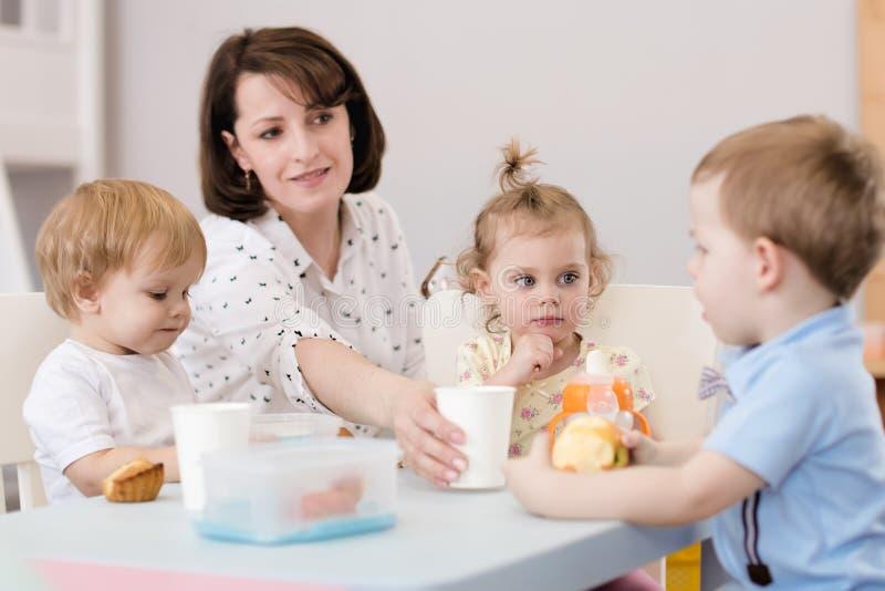 Dzieciaki lunch z nauczycielem w pepinierze zdjęcie royalty free