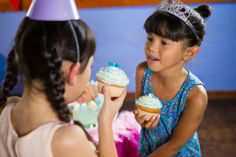 Dzieciaki ma babeczkę podczas przyjęcia urodzinowego fotografia royalty free