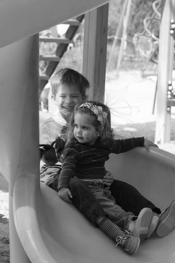 Dzieciaki ma zabawę przez włosianego dźwigania statycznej elektryczności na plastikowym boiska obruszeniu portret piękna czarny b fotografia royalty free