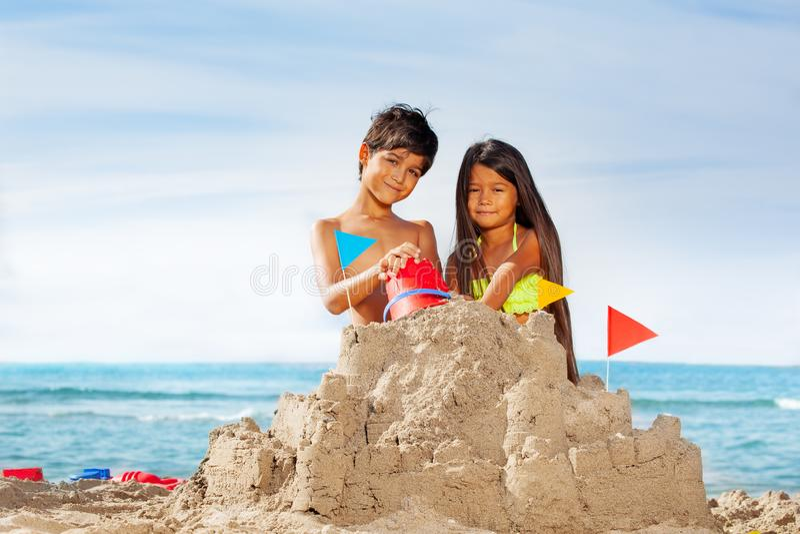 Dzieciaki ma zabawa budynku sandcastle na plaży obraz royalty free