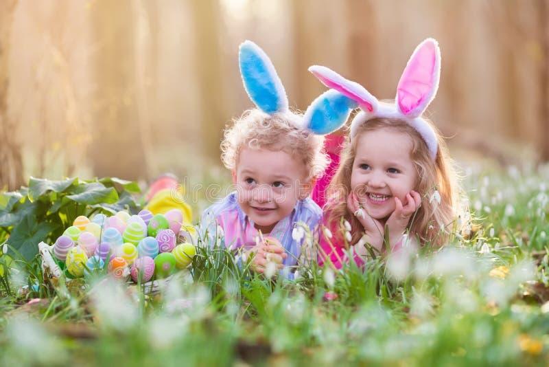 Dzieciaki na Wielkanocnego jajka polowaniu w kwitnącej wiośnie uprawiają ogródek fotografia royalty free