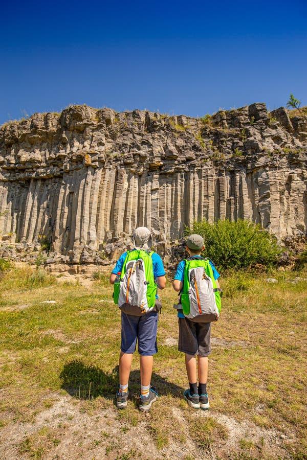 Dzieciaki patrzeje powulkanicznego bazaltowego coloumn obrazy royalty free