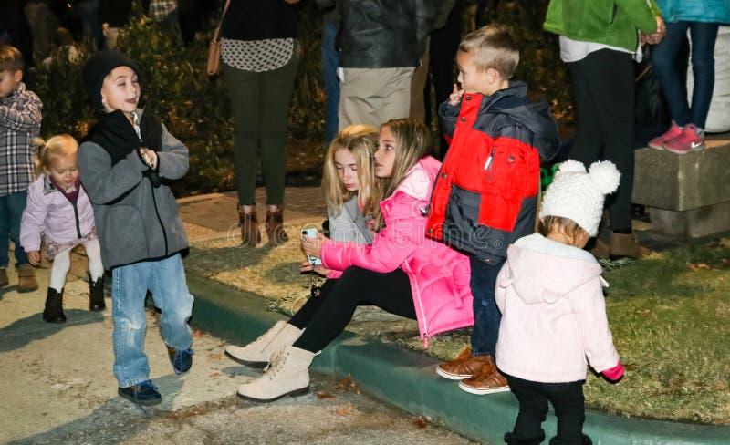 Dzieciaki patrzeje telefon i bawić się przy Bożenarodzeniową oświetleniową ceremonią w Tulsa Oklahoma usa 11-23-2017 zdjęcie royalty free