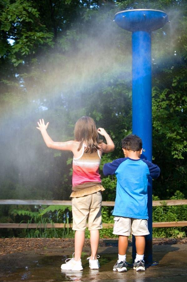 Dzieciaki plaing przy plenerową prysznic obraz royalty free