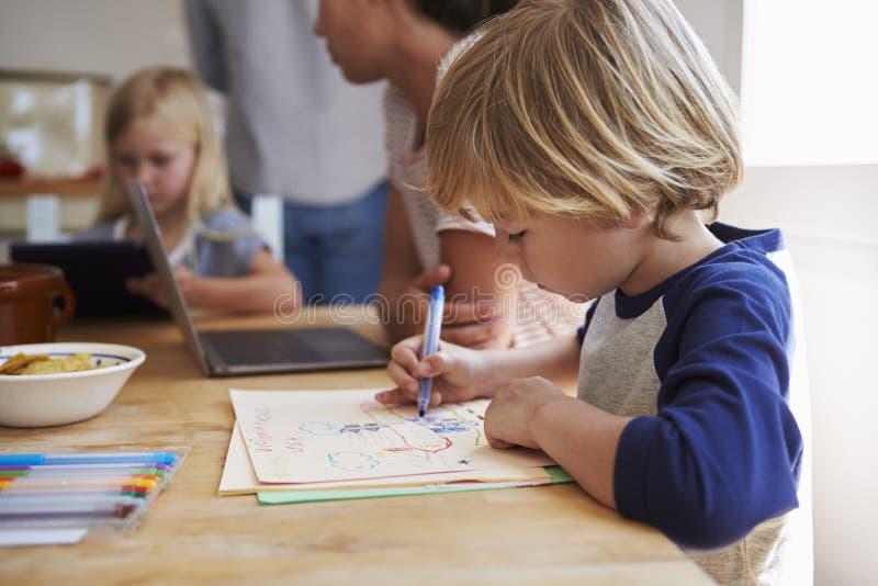 Dzieciaki pracuje przy kuchennym stołem z ich matką, zamykają up obraz royalty free