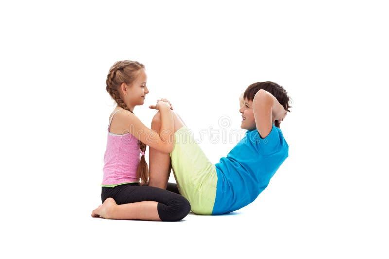 Dzieciaki robi abs ćwiczą wpólnie - pomagać each inny obraz stock