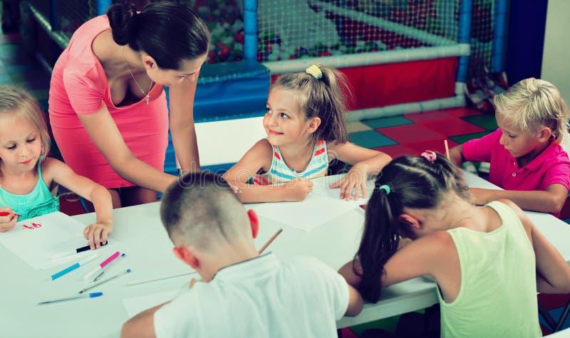 Dzieciaki rysuje wraz z adiunktem przy hobby grupą fotografia royalty free