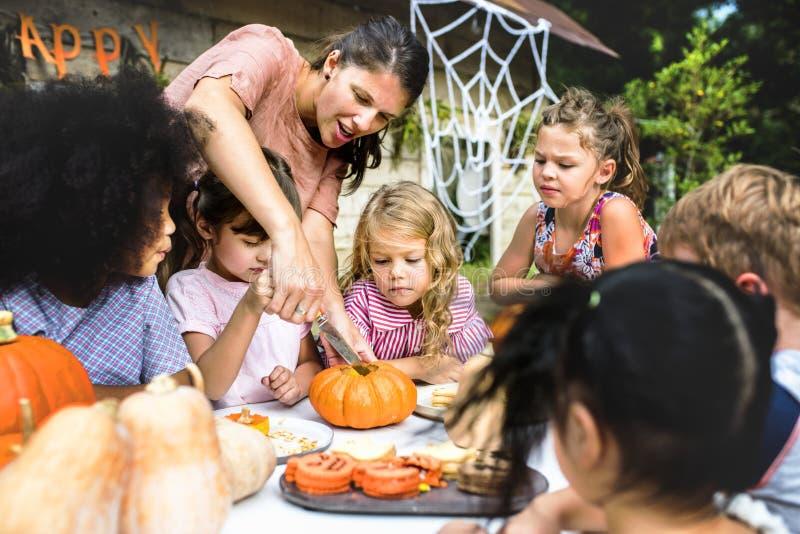 Dzieciaki rzeźbi Halloweenowego Jack ` - lampiony fotografia royalty free
