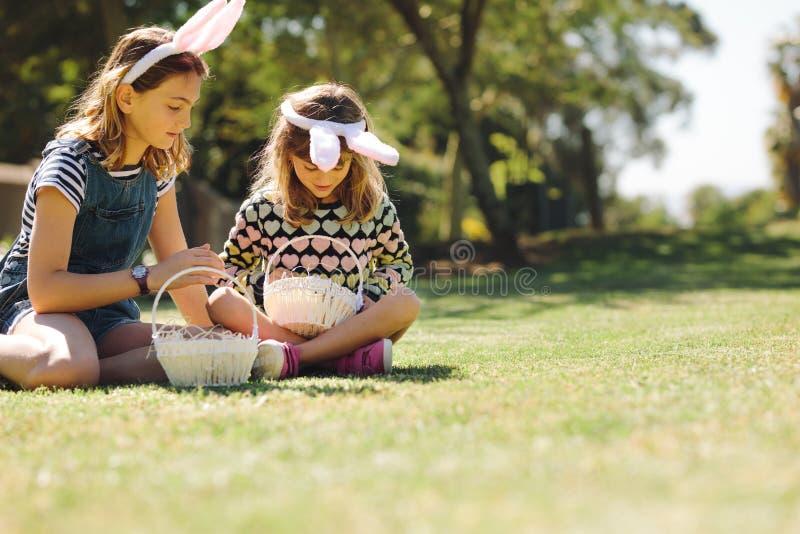 Dzieciaki siedzi w bawić się i ogródzie obraz stock