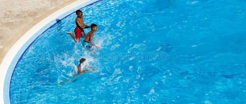 Dzieciaki skacze wewnątrz pływackiego basenu rywalizacja obrazy stock