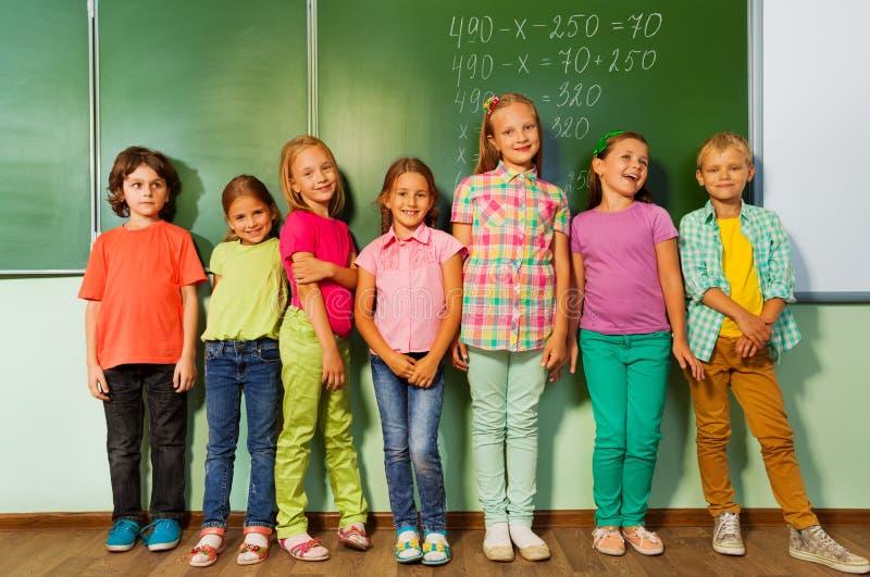 Dzieciaki stoją w linii blisko uśmiechu i blackboard zdjęcia stock