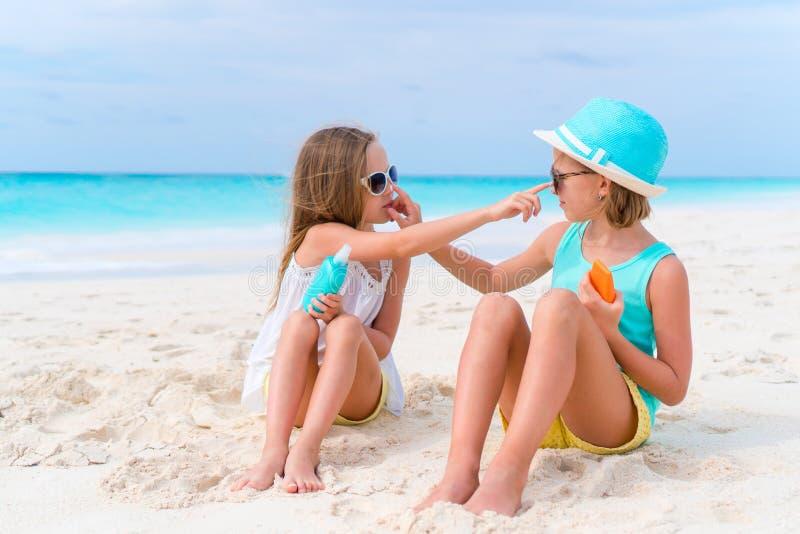 Dzieciaki stosuje słońce śmietankę each inny na plaży Pojęcie ochrona od pozafioletowego napromieniania zdjęcie stock