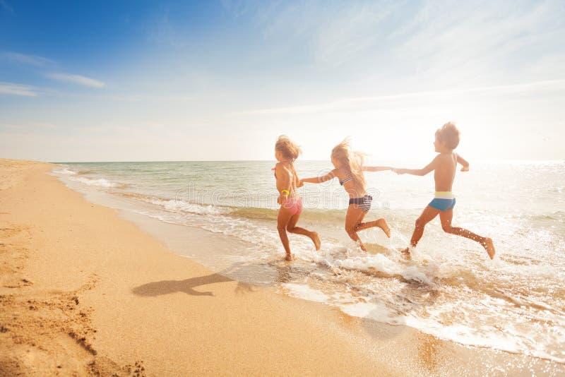 Dzieciaki trzyma ręki i bieg wzdłuż piaskowatej plaży fotografia royalty free