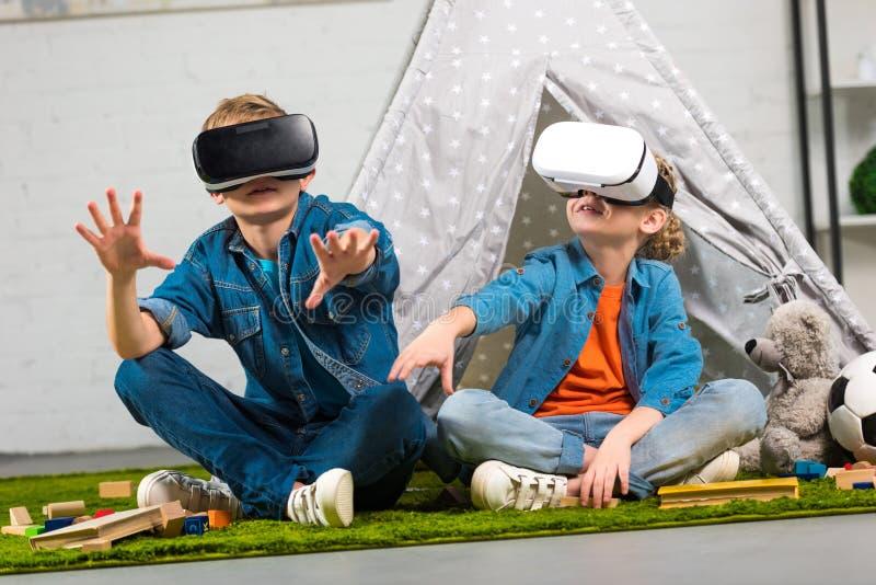 dzieciaki używa rzeczywistość wirtualna słuchawki i gestykulujący rękami zbliżają wigwam obraz royalty free