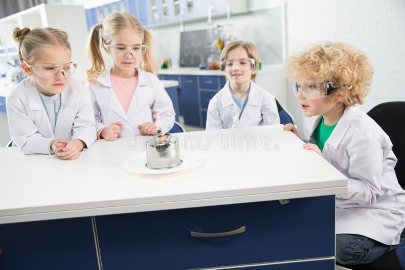 Dzieciaki w lab żakietach i ochronnych glases robi eksperymentowi zdjęcia royalty free
