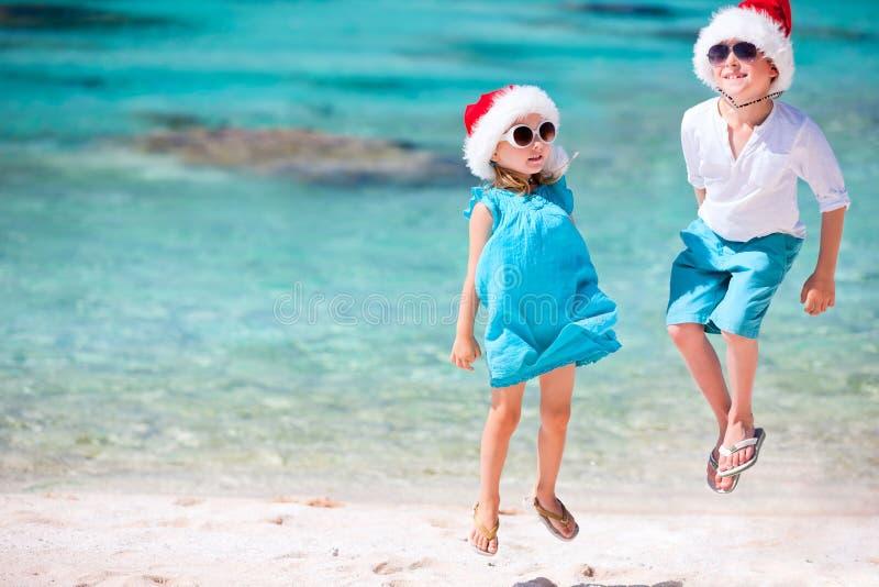 Dzieciaki w Santa kapeluszach przy plażą fotografia royalty free