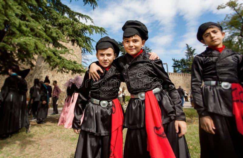 Dzieciaki w tradycyjnych Gruzińskich kostiumach ma zabawę podczas miasto festiwalu wpólnie obraz stock