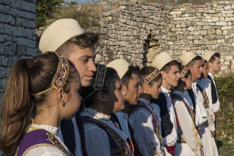 Dzieciaki w typowym Krajowym kostiumowym festiwalu muzyki w Berat roszują w Albania obraz royalty free