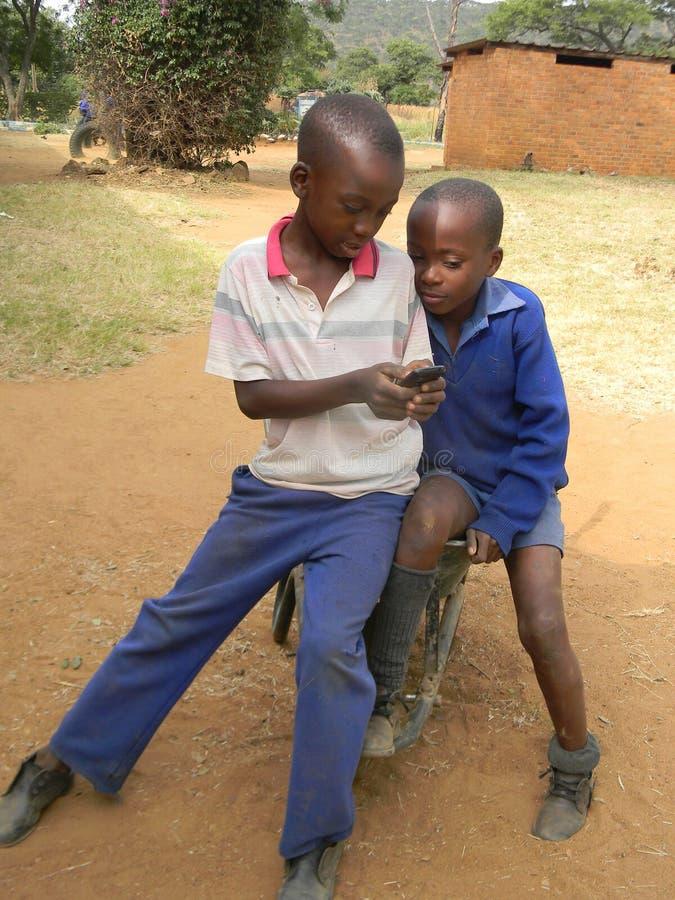 Dzieciaki wyszukuje telefon komórkowego w wheelbarrow zdjęcia stock