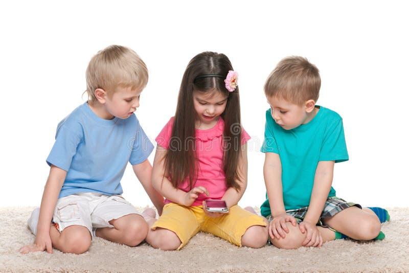 Download Dzieciaki Z Gadżetem Na Białym Dywanie Zdjęcie Stock - Obraz złożonej z przyjaźń, eurydice: 41951424