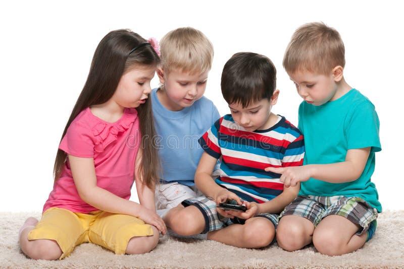 Dzieciaki z gadżetem na dywanie zdjęcie stock
