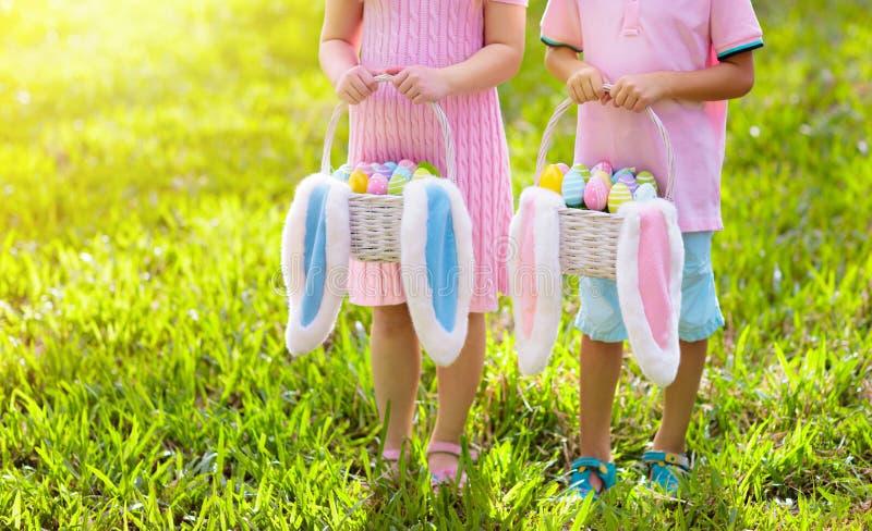 Dzieciaki z jajkami koszykowymi na Wielkanocnym jajku tropią obrazy royalty free