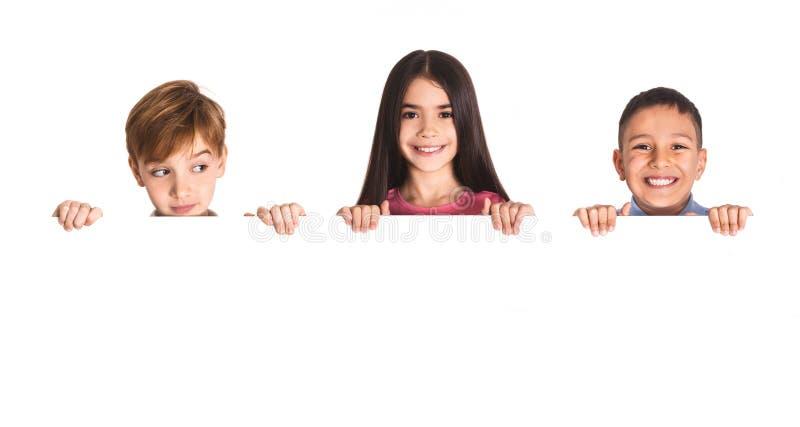 Dzieciaki z pustą deską odizolowywającą na bielu zdjęcia royalty free