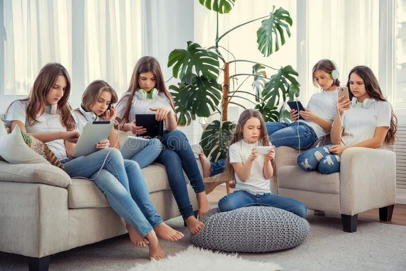 Dzieciaki z telefonami i pastylkami, z smartphones i hełmofonami Grupa nastoletnie dziewczyny używa gadżety obrazy royalty free