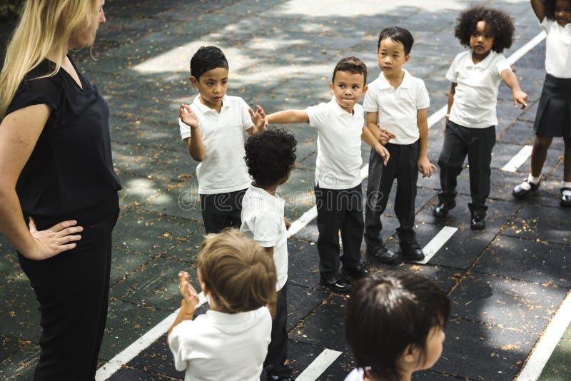 Dziecinów ucznie stoi wpólnie w linii fotografia stock