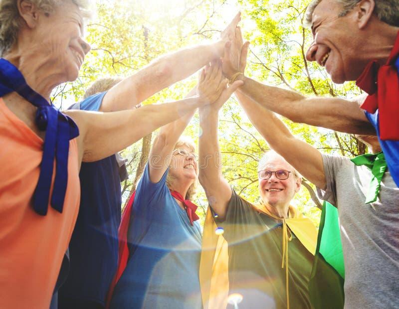 Dziecinni seniorów bohaterzy daje wysocy pięć obrazy stock
